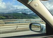Gruyere land in the car's mirror