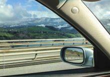 Gruyere land in the car's mirror